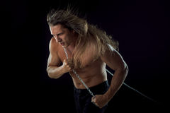 Young man with long hair dragging something behind him. Strong. Young man with long hair dragging something behind him royalty free stock images