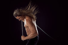 Young man with long hair dragging something behind him. Strong. Young man with long hair dragging something behind him stock image
