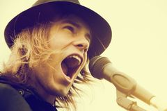 Young man with long hair and hat shouting to microphone. Vintage, music Royalty Free Stock Photography