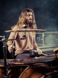 Young man with long hair playing drums. Photo of a young male drummer with long hair playing his drum set. Filtered for vintage look Stock Image