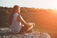 Young man with long hair sits at sunset on the edge of cliff or rock Stock Images