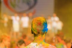 A young man with long hair strewn with red colored paint celebrates the Holi festival. Dnipro city, Dnepropetrovsk royalty free stock photos
