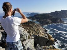 Young man with long hair taking a picture of cies island coast Stock Photography