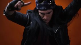Rocker guy jamming out to music and showing the sign of the horns, slow motion. Young man with long hair, wearing leather jacket and spiked gloves, enjoying stock footage