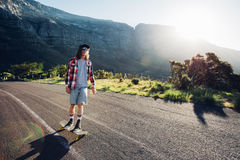Young man longboarding outdoors on rural road Stock Image