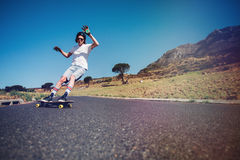 Young man longboarding on a road Stock Image