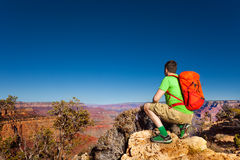 Young man look at grand Canyon sit on squads Royalty Free Stock Photos
