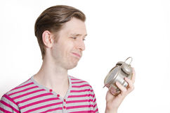Young man looking at alarm clock Stock Images