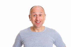 Young man looking amazed in to the camera. Young baldheaded man in front of white background looking amazed in to the camera Stock Photo