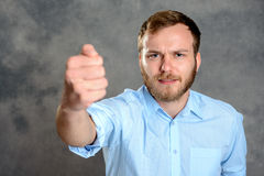 Young man looking angry and showing fist Royalty Free Stock Photography