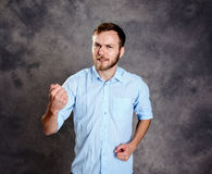 Young man looking angry and showing fist Stock Photo