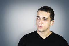 Young man looking aside over neutral blue background Stock Images