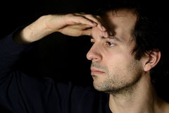 Young man looking away, with a hand on the forehead Royalty Free Stock Photos