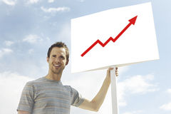 Young man looking away while holding arrow signboard against cloudy sky Stock Photos