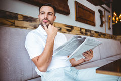 Young man looking away while holding a newspaper Stock Photos