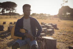 Young man looking away while sitting with guitar Stock Photography