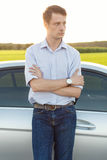 Young man looking away while standing by car at countryside Stock Images