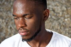 Young man looking away with sweat dripping down face Royalty Free Stock Photography