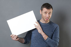 Young man looking awful in holding a bad news on his board with space for any negative text Stock Image