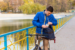 Young Man Looking Through Backpack on Bike in Park Stock Photos