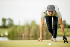 Young man looking at ball while crouching on golf course Stock Image