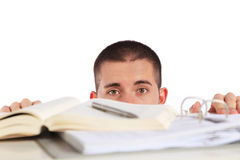 Young man looking behind his study documents. Attractive young man looking behind his study documents. All isolated on white background Stock Images