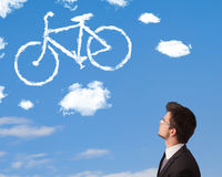 Young man looking at bicycle clouds on blue sky Stock Image