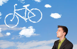 Young man looking at bicycle clouds on blue sky Royalty Free Stock Photos