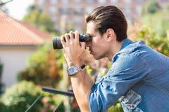 Young man looking through binocular searching Stock Photos