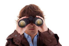 Young man looking through binoculars. With symbol of money, isolated on white, studio shot Royalty Free Stock Photo