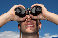 Young man looking with binoculars Royalty Free Stock Photo