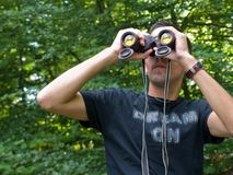 Young man looking through binoculars Stock Photography