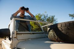 Young man looking through binoculars standing in off road vehicle Stock Image