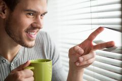 Young man looking through blinds. Man looks through jalousie and holding tea cup Royalty Free Stock Photography
