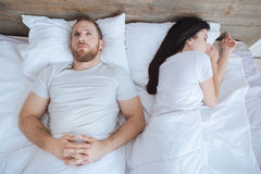 Young man looking at ceiling while his wife sleeping. Cannot stop thinking about it. Millennial bearded men lying in bed and thinking about something while his Royalty Free Stock Photography