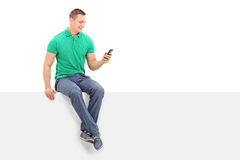 Young man looking at a cell phone seated on panel Royalty Free Stock Images