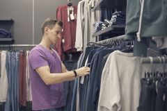 Young man is looking for clothes in the clothing shop.  Royalty Free Stock Images