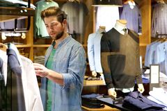 Young man looking at clothes to buy at shop. Portrait of a young man looking at clothes to buy at shop Stock Images