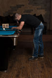 Young Man Looking Confused At Billiard Table Royalty Free Stock Photos