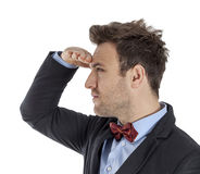 Young Man Looking in the Distance. Profile of a handsome young man with a red bow looking in the distance against a white background Royalty Free Stock Photography