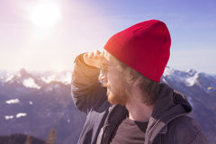 Young man looking into the distance surrounded my mountains Royalty Free Stock Image