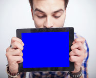 Young man looking down while holding a tablet pad computer Royalty Free Stock Image