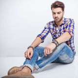 Young Man Looking Down While Sitting On The Floor Royalty Free Stock Photography
