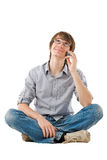 Young man looking dreamy with mobile phone Royalty Free Stock Photos
