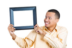 A young man looking at an empty frame in a funny way Stock Photography