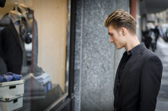 Young Man Looking at Fashion Items in Shop Window. Handsome Young Man in Black Elegant Suit Looking at Displayed Fashion Items in Glass Window Boutique at the stock photo