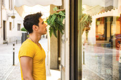 Young Man Looking at Fashion Items in Shop Window Royalty Free Stock Photography