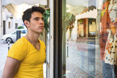 Young Man Looking at Fashion Items in Shop Window Royalty Free Stock Images