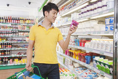 Young Man Looking At Food in Supermarket Stock Image