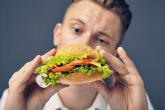 Young man looking at a fresh burger. Beautiful Young man looking at a fresh burger Stock Photography